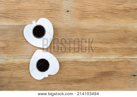 Two Coffee Cups With Heart Shaped Saucer On Wooden Background