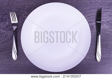 Empty plate fork and knife isolated on wooden table.
