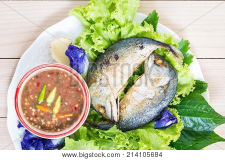 Fried two mackerels with vegetable on white on wooden table