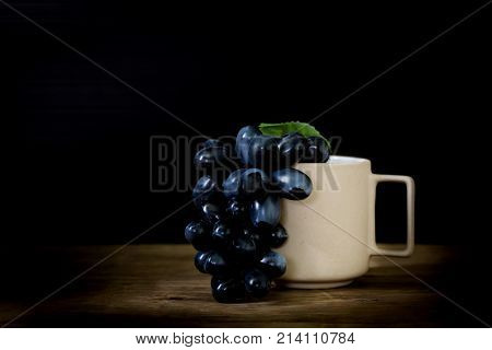 Grape With Ceramic White Cup On Wooden Floor