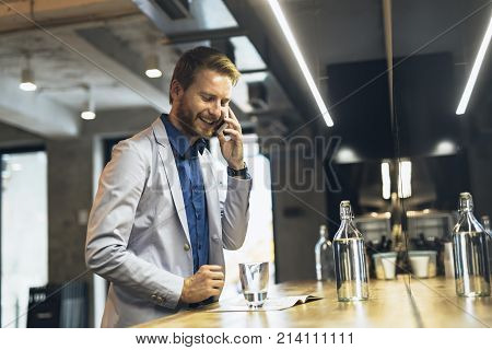 Handsome smart businessman using cellphone to call