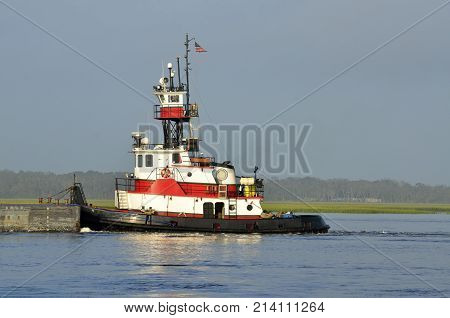 Tug boat pushing a barge on the river at St. Augustine, Florida