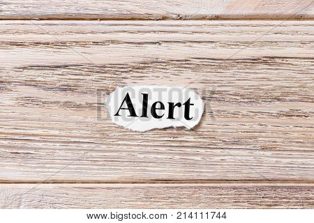 ALERT word on paper. concept. Word ALERT on a wooden background.