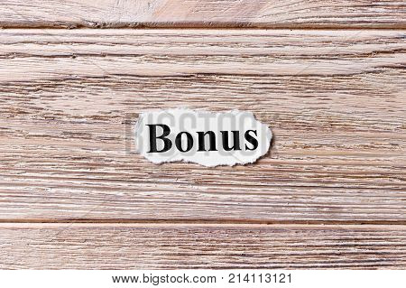 BONUS of the word on paper. concept. Words of BONUS on a wooden background.