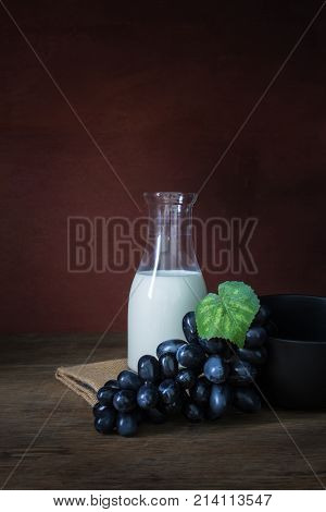 Bottle of milk with grapes and black wowl on wooden floor in still life shot