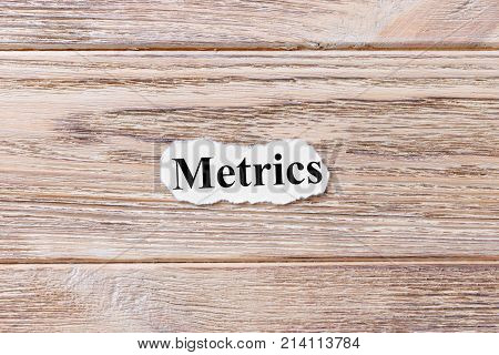 Metrics of the word on paper. concept. Words of Metrics on a wooden background.