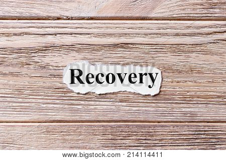 Recovery of the word on paper. concept. Words of Recovery on a wooden background.