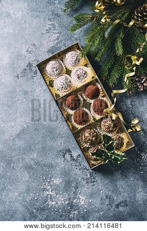 Variety of homemade dark chocolate truffles with cocoa powder, coconut, walnuts as Christmas gift in golden box, fir tree, Christmas decorations above over blue background. Top view, copy space. Toned