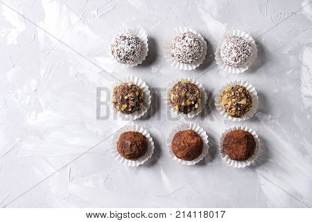Variety of homemade dark chocolate truffles with cocoa powder, coconut, walnuts in row over gray texture background