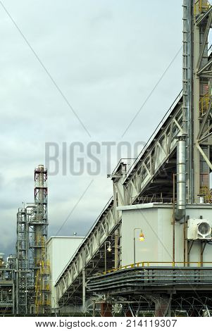 a fragment of some large refinery with a variety of technical designs a fractionating column a covered conveyor structure and burning lanterns