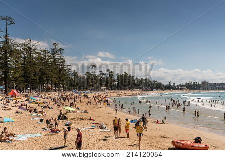 Sydney Australia - March 26 2017: North section of Manly Beach with sand and Tasman Sea. People on the sand and in the water. Condominiums and green belt.
