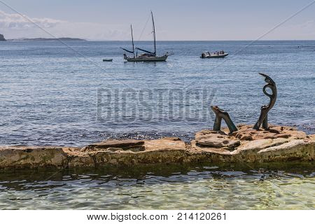 Sydney Australia - March 26 2017: Oceanides statue on rock in Tasman Sea in front of Manly beach by Helen Leele. Two small boats idle in water.