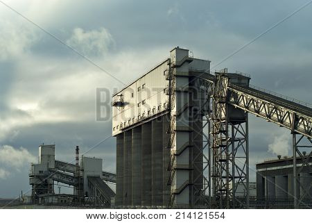 a fragment of a modern industrial enterprise with several silos for storage of loose materials and an inclined covered belt conveyors