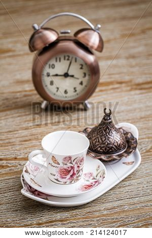 Turkish style coffee set served on a tray and an alarm clock