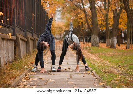 A young couple are doing sports in the park, making leans forward by lifting one arm inwards and looking at each other. Outdoors.