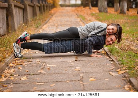 A loving sports couple lead an active lifestyle, doing sports in an autumn park. The guy presses with the girl on the back. Outdoors.