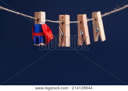 Toy clothespin peg superhero on clothesline. Brave leadership character with team blue background. soft focus. macro view, shallow depth of field