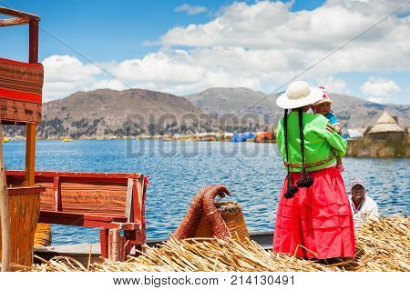 Titicaca lake Puno Peru - March 20 2017. Woman in traditional dresses with a child on Uros floating islands on Titicaca lake in Puno Peru South America