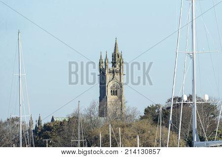 Fairhaven Massachusetts USA - November 15 2017: Tower of Unitarian Church looms over boat masts at marina in Fairhaven Massachusetts
