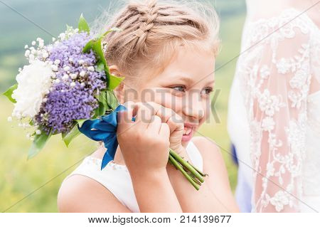 A cute little touching girl and an amazing white wedding bouquet of purple pions on outing registration in nature at her parents' wedding