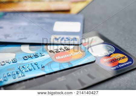 KIEV, UKRAINE - OCTOBER 2, 2017: Different Visa and MasterCard credit cards on grey background