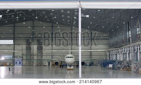 Roller shutter door and concrete floor of airport hangar and airplane background. Airport hangar from the outside with big tall doors. Front view. Aircraft Hangar 4K