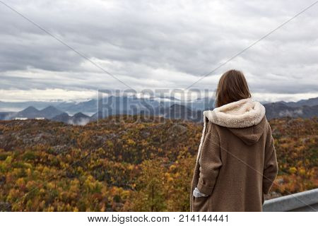 Girl standing backwards and watching rainy autumn season mountain landscape with cloudy sky