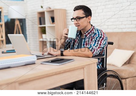 A young disabled man works at home. He sits in a wheelchair at his desk. On the desk is a laptop. A man works as a freelancer with the help of the Internet.