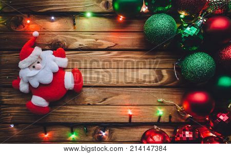 Christmas decorations. Christmas background with Santa Claus Christmas balls and garland with colored lights on a brown wooden board. Postcard concept.