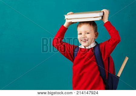 Cheerful Thoughtful Little School Boy In School Uniform With Backpack And Big Pile Of Books Standing