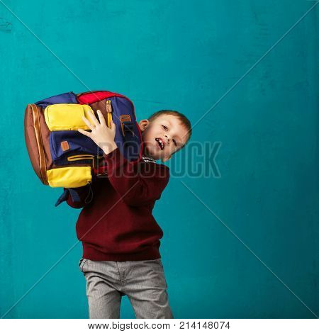 Cheerful Thoughtful Little School Boy In School Uniform With Big Backpack Standing Against Blue Wall