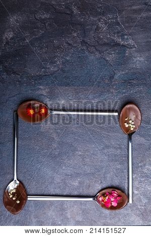 Spoons with frozen chocolate with flowers and petals in them. Spoons lies in the form of a square