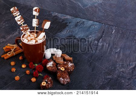 A cup of hot chocolate with marshmallows in chocolate on a stick next to hazelnuts, flowers, marshmallow and cinnamon sticks