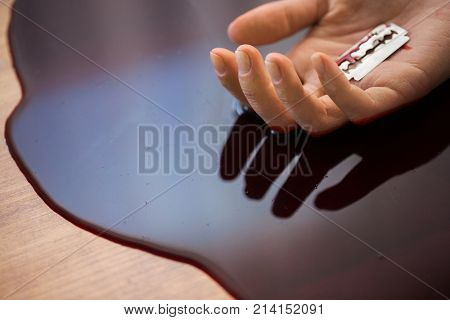suicide, death and people concept - close up of dead woman hand in blood on floor at crime scene
