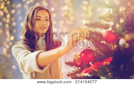 x-mas, winter holidays and people concept - happy young woman decorating christmas tree at home