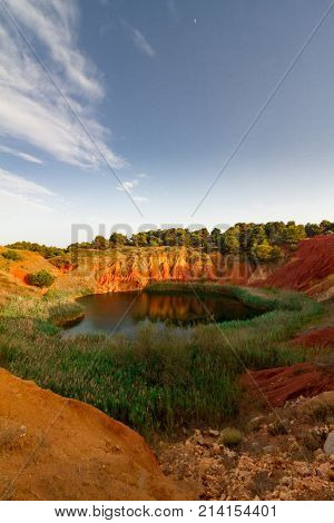 This lake was a Bauxite (mineral used to produce aluminium) mine until 1976 when it has been abandoned due to the infiltration of salted water coming from the sea that has created the lake. It is located in Otranto a city of the Puglia region Italy.