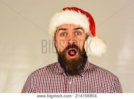 Guy In Plaid Shirt And Santas Hat With White Pompon.