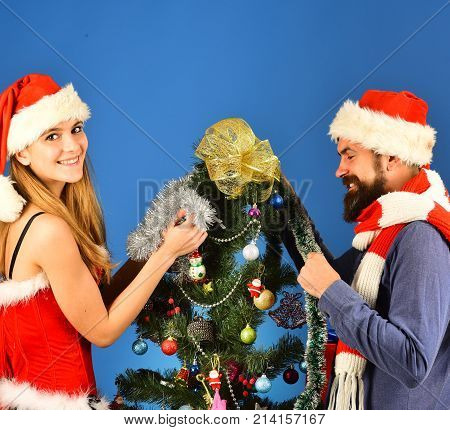 Christmas Time And Love Concept. Couple In Love Decorates Tree