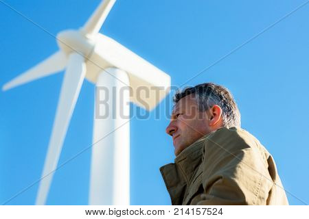 Man's portrait outdoor against blue sky with wind turbine