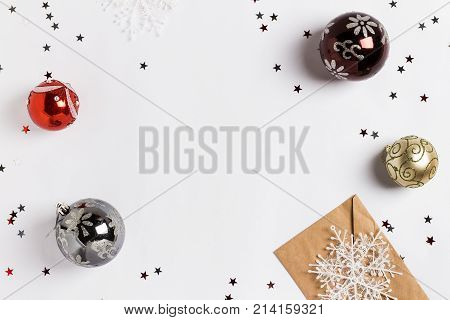 Christmas decoration composition greeting card envelope snowfalls balls glitter stars on white festive table isolated. New year winter holiday xmas. Top view flat lay copy space