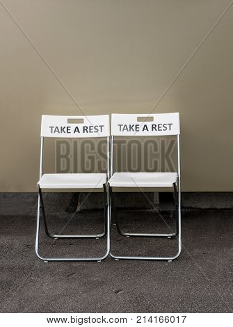 Pair of folding plastic chairs with the message Take a Rest engraved on the backrest