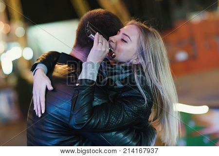 Young happy couple drinks whiskey alcohol from flask. Outdoors at night in an amusement park. Night city background