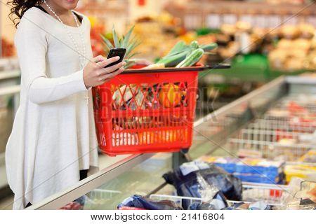 Frau mit roten Korb mit Handy im Shop einkaufen