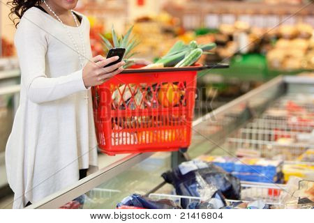 Femme avec panier rouge avec GSM dans shopping magasin