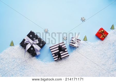 Gift boxes on decorative snow with snowflakes and small Christmas trees on a laconic blue background. The concept of winter holidays. Template for greeting cards.