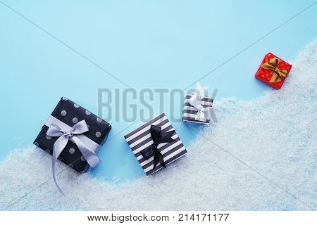 Gift boxes on decorative snow, on a laconic blue background. The concept of winter holidays. Template for greeting cards.