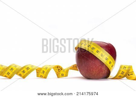 Yellow measure tape around a red apple as a weight loss concept