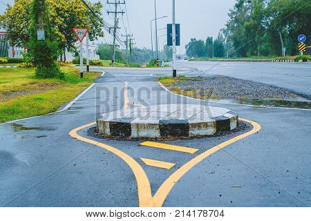 Traffic circle on the road a junction which traffic moves in one direction around a central island and Thai text in the red frame on triangle traffic symbol means the yield sign.