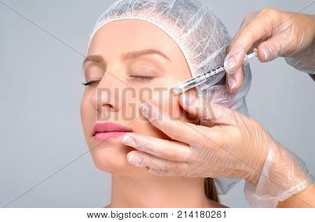 Woman Is Getting Filler Injection In Cheeks. Anti-aging Treatment And Face Lift. Cosmetic Treatment