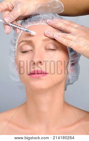 Woman Is Getting Injection In Forehead. Anti-aging Treatment And Face Lift. Cosmetic Treatment And P